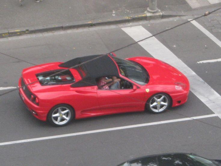 Red Ferrari 360 Spider driving through Melbourne.