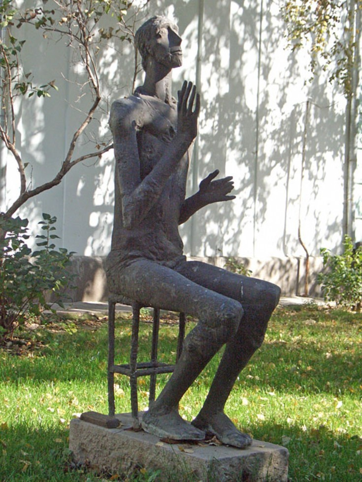 Statue of seated man looking upwards